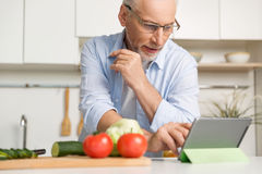 Concentrated mature man wearing glasses cooking salad royalty free stock photos