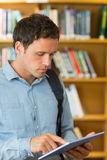 Concentrated mature student using tablet PC in library Royalty Free Stock Photography
