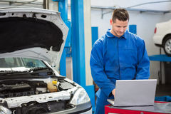 Concentrated mechanic using his laptop Stock Photography