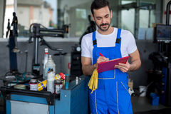 Concentrated mechanic writing on clipboard Stock Image