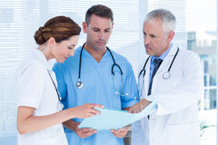 Concentrated medical colleagues analyzing file together. In the hospital royalty free stock images