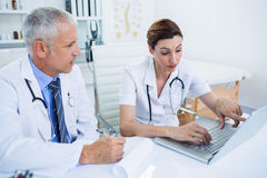 Concentrated medical colleagues discussing and pointing on laptop screen Royalty Free Stock Photo
