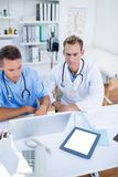 Concentrated medical colleagues discussing and working with laptop Stock Photo