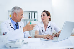 Concentrated medical colleagues discussing and working with laptop Royalty Free Stock Photos