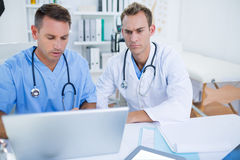 Concentrated medical colleagues working with laptop Stock Photo