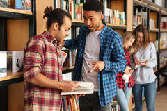 Concentrated men students standing in library reading book. Picture of young concentrated men students standing in library reading book. Looking aside royalty free stock image