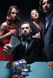Concentrated men and women playing poker in casino stock photos