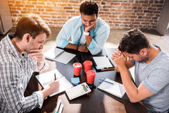 Concentrated men working on project at small office meeting. Young concentrated men working on project at small office meeting royalty free stock photography