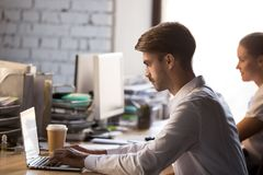 Focused male employee busy working at laptop in coworking office stock photography