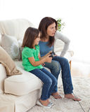 Concentrated mom and daughter playing video games. Together in the living room Stock Photography
