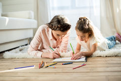 Concentrated mother and daughter drawing picture at home Royalty Free Stock Photo