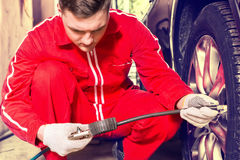 Concentrated motor mechanic checking the air pressure of a tyre. Crouching down alongside the vehicle with the gauge from the pump in his gloved hand Royalty Free Stock Images