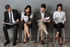 Concentrated multicultural business people with folders and notebooks waiting. For job interview royalty free stock photos