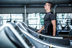Concentrated muscular man using treadmill Stock Photo
