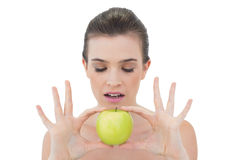 Concentrated natural brown haired model holding a green apple Royalty Free Stock Images