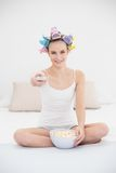 Concentrated natural brown haired woman in hair curlers watching tv while eating popcorn Stock Image