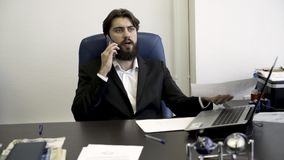 Concentrated, nervous, young, bearded businessman on the phone, sitting in blue leather armchair in the office. Angry