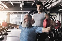 Serious mature male is having workout in gym stock images