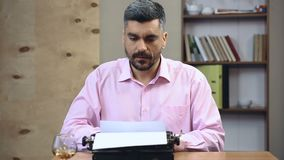 Concentrated old-school author typing book on vintage typewriter in his office. Stock footage stock footage