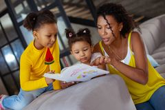 Concentrated parent reading useful book for daughters stock photos