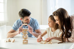 Concentrated parents playing jenga game with daughter Stock Photo