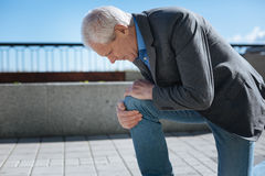 Concentrated pensioner suffering from knee ache in the park Stock Photography