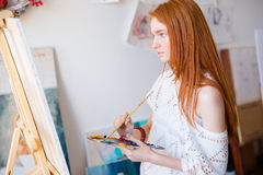Concentrated pensive woman painter with long hair painting on canvas Stock Photos
