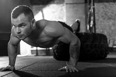 Concentrated persistent bodybuilder doing push ups. Involved in training. Concentrated persistent brutal man putting legs on a giant tire and doing push ups Stock Image