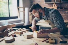 Concentrated persistent talented professional carpenter bearded. Wearing casual checkered shirt apron safety glasses is measuring the length on wooden box`s Royalty Free Stock Photos