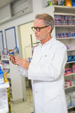 Concentrated pharmacist looking at medicine Royalty Free Stock Photo
