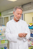 Concentrated pharmacist looking at medicine Royalty Free Stock Photos