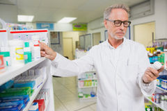 Concentrated pharmacist looking at medicine. In the pharmacy Royalty Free Stock Image