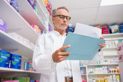 Concentrated pharmacist reading documents Stock Images