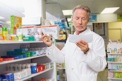 Concentrated pharmacist reading prescription Royalty Free Stock Image