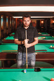 Concentrated player with a cue in  billiard room. Royalty Free Stock Photography