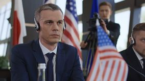 Concentrated politician listening to translation on conference. Adult man of American deputy wearing headphones and listening to speech translation while sitting stock video footage
