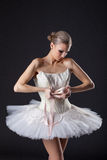 Concentrated pretty ballet dancer kneads pointe Stock Image