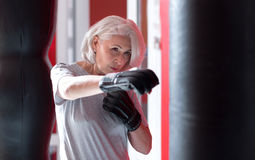 Concentrated pretty gray haired woman boxing in a gym. Stock Images