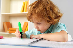 Concentrated pupil sitting with marker. Childhood and learning concept, intelligent little artist drawing on paper with highlighter Royalty Free Stock Photography