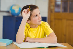 Concentrated pupil working at his desk in a classroom Stock Images