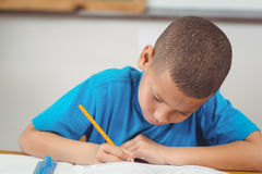 Concentrated pupil working at his desk in a classroom Royalty Free Stock Photos