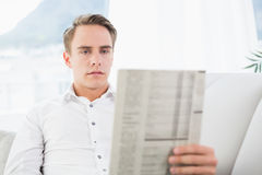 Concentrated relaxed man reading newspaper on sofa Stock Photos