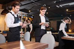 Concentrated restaurant manager checking online records on table stock photos