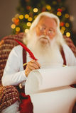 Concentrated santa writing list on the armchair Royalty Free Stock Photo
