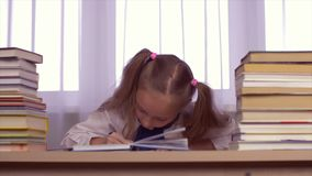Concentrated school girl thinking about homework and rejoicing new though. Concentrated school girl at table thinking about homework and rejoicing new thought stock video footage