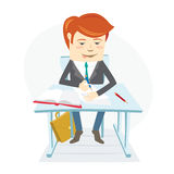 Concentrated school student writing at the desk on his lessons i Stock Photos