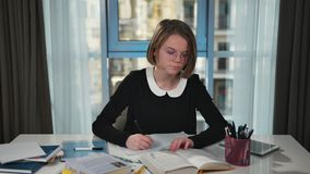 Concentrated schoolgirl doing homework. Reads a book and writes in an exercise book at home stock footage