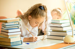 Concentrated schoolgirl surrounded by books doing homework Stock Image