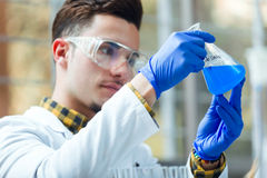 Concentrated scientist making experiment in laboratory. Portrait of concentrated scientist making experiment in laboratory Royalty Free Stock Photos