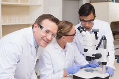 Concentrated scientists working together with microscope Stock Photo